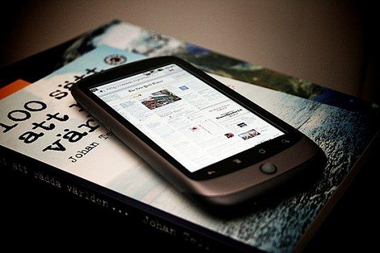 Valokuvassa matkapuhelin lehden päällä.